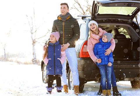 En altfor glad familie som står foran en bil